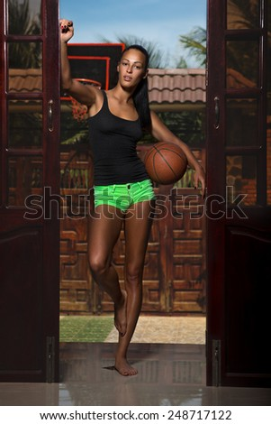 Woman with basket ball at home - stock photo