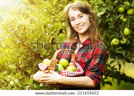 Woman with basket full of ripe apples in a sunny garden. Young smiling attractive woman is standing with full basket of organic apples in a sunlit orchard. Country happy lifestyle concept.
