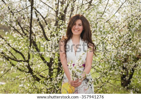 Woman with beautiful hair in the lush spring garden smiling and rejoicing, beauty, makeup, hair - stock photo