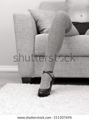 Woman with beautiful legs sitting on sofa. Black and white. - stock photo