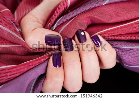Woman with beautiful purple nails gripping a colour matched maroon and purple fabric to show them off to best advantage - stock photo