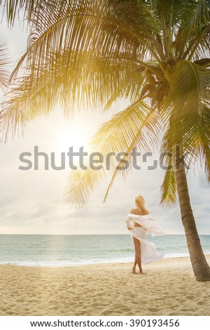 woman with beautiful sarong on tropical beach - stock photo