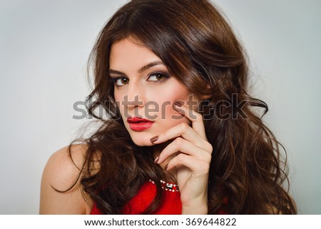 Woman with beauty long brown hair and red lips in red dress