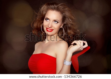 Woman with beauty long brown hair  wearing in red holding shoe over dark - stock photo