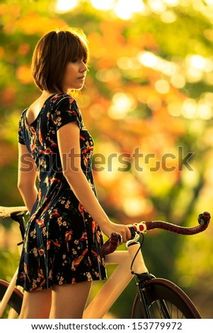 woman with bicycle in the garden. - stock photo