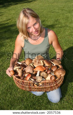 Woman with big basket full of mushrooms on green grass - stock photo