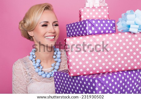 Woman with big beautiful smile holding colorful gift boxes. Soft colors. Christmas, birthday, Valentine day, presents. Studio portrait over pink background  - stock photo