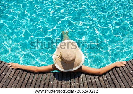 Woman with big hat relaxing on the swimming pool  - stock photo