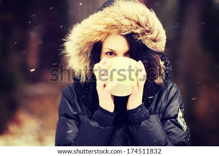 Woman with big mug of hot drink during cold day.  - stock photo