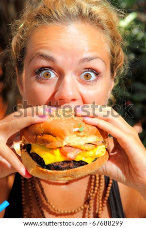 Woman with big round eyes eating a yummy cheeseburger - stock photo