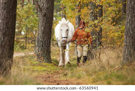 Woman with big white horse in forest - stock photo
