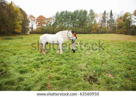 Woman with big white shire white horse in pasture - stock photo