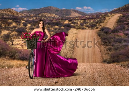 Woman with bike in a beautiful pink dress - stock photo