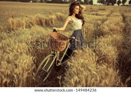 Woman with bike resting on wheat field at sunset - stock photo