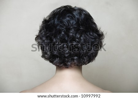 Woman with black curly hair on beige texture background