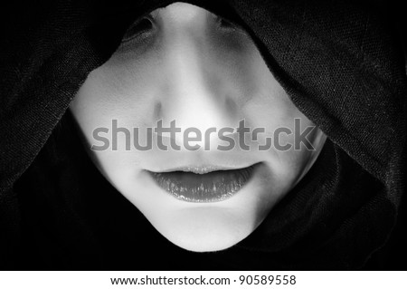 Woman with black hood, focus on her lips - stock photo
