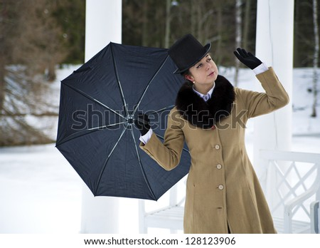 Woman with black umbrella feeling winter wind flow