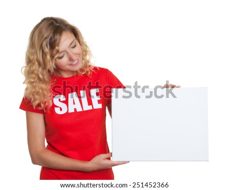 Woman with blond hair in a sale shirt showing to a signboard - stock photo