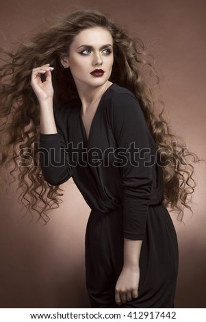 Woman with blowing hairs looking away from camera on brown background in studio photo