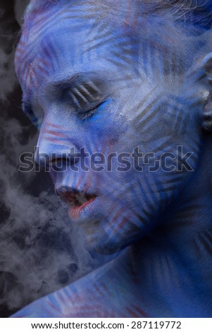 woman with blue face art on dark background with smoke - stock photo