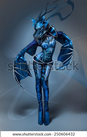 Woman with Blue Painted Skin in dragon costume - stock photo