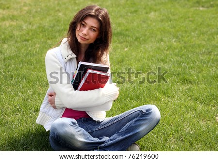 Woman with book in green grass on summer park - stock photo