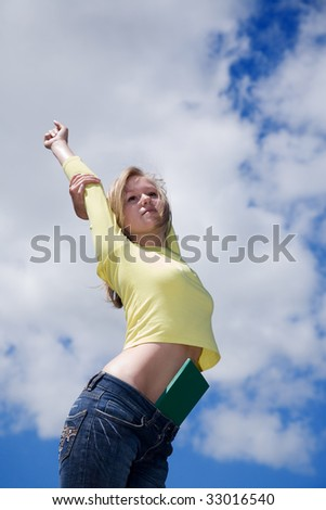 woman with book on cloudy sky background