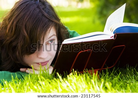 Woman with book reading in the park. - stock photo