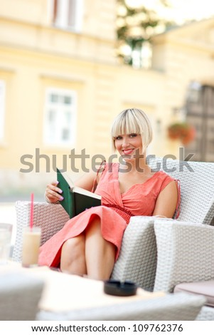 woman with book sitting in cafe chair - stock photo