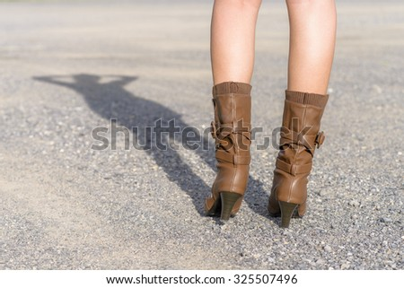 Woman with boot waiting on the road; Shadow shown; Low angle shot