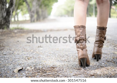 Woman with boot walking on the road - stock photo