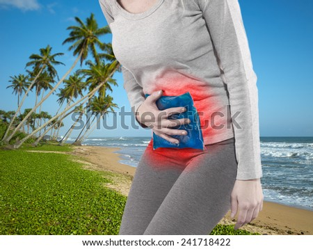 Woman with both palm around waistline to show pain and injury on belly area.  - stock photo