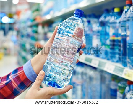 Woman with bottle drinking water in shop