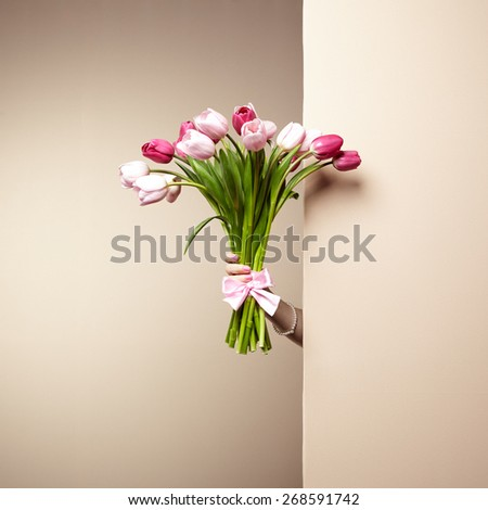 Woman with bouquet of flowers in her hands. Flowers. Spring. Tulips. March 8. Fashion photo - stock photo