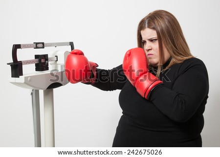 woman with boxing gloves fighting against a medical weight scale. - stock photo