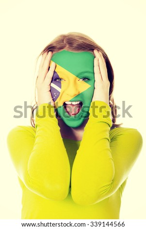 Woman with Brazilian flag painted on face. - stock photo