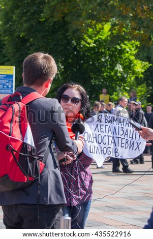 """Woman with broadsheet """"Require homosexual marriage"""" being interviewed. Kiev pride gay parade, 12.06.2016. - stock photo"""