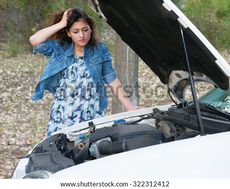 Woman with broken car inspecting engine