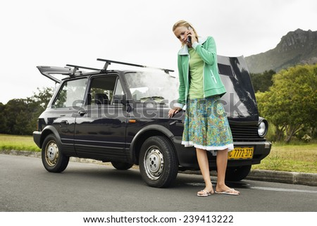 Woman with Broken Down Car - stock photo