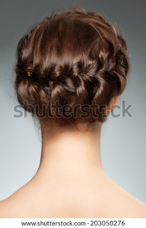 Woman with brunette hair and braid hairdo. Rear view, hairstyle with tress - stock photo