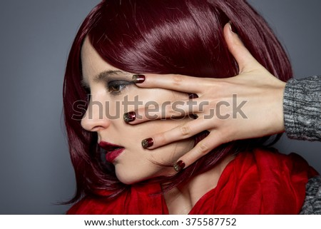 Woman with burgundy red hair and scarf showing nail polish art or manicure design.  The nail art is a stick on design with glitters.
