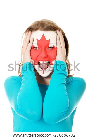 Woman with Canada flag painted on face. - stock photo