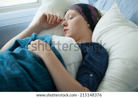 Woman with cancer resting in bed, horizontal - stock photo