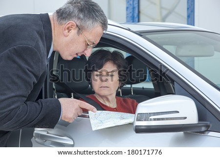 Woman with car and map asks for the way - stock photo