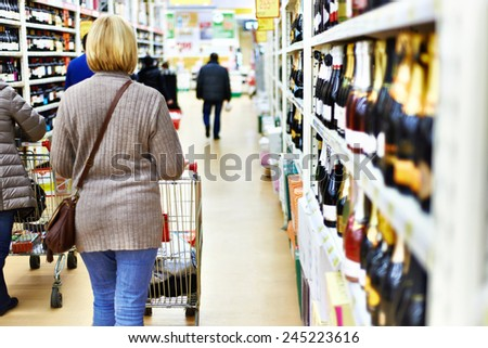 Woman with cart as supermarket shopper - stock photo