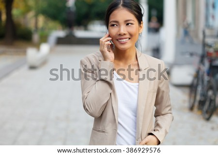 Woman with cellphone on walking on the street - stock photo