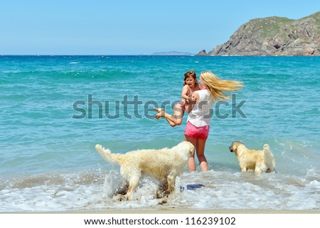 woman with child and dog on the beach - stock photo