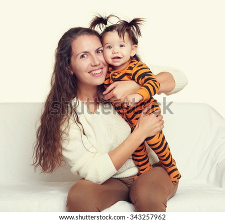 woman with child girl portrait sitting on sofa and playing - stock photo