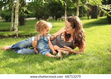 Woman with child having fun in summer park
