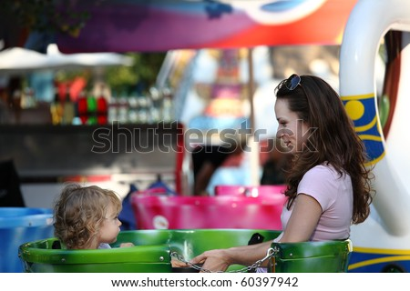 Woman with child on carousel - stock photo